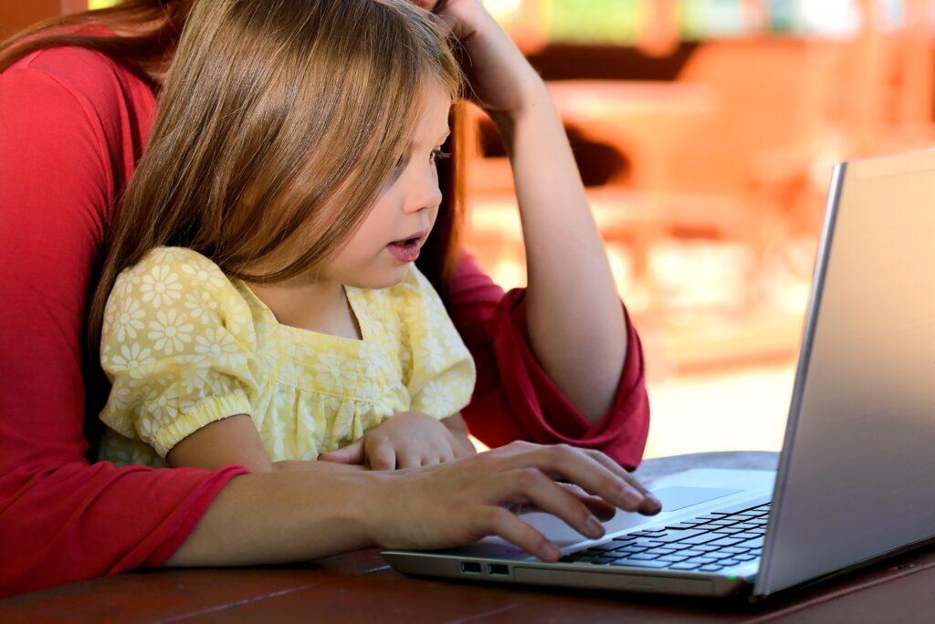 Mädchen mit Mutter vor dem Laptop, Kuren beantragen, Caritas