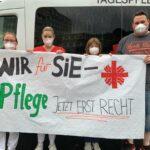"""Mitarbeitende der Caritas mit einem Banner """"Wir für Sie - Pflege jetzt erst recht"""""""