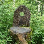 Aus einem Baumstumpf gefertigter Stuhl in einem Wald
